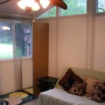 Front room showing futon, one closet, eaves' windows, overhead fan and windows toward front yard.