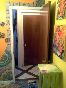the picture is odd - you are looking our the bathroom door to the hall (tile and wood) and basement door.  Around the bathroom door is one of the first architectural tiles work that I made after learning how.